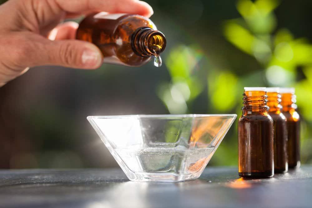Goteo de aceite esencial en un recipiente de vidrio