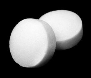 Bolas de naftaleno blanco sobre fondo oscuro.