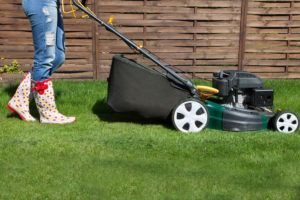 Mujer cortadora con cortadora de césped en el jardín