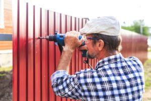 Un anciano con un taladro construye una valla de metal