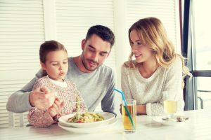 Familia feliz comiendo pasta en la mesa
