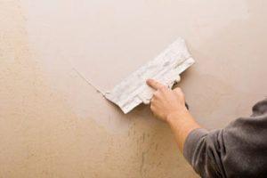 Un hombre está sellando las grietas de la pared