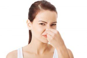Retrato de un joven mujer sosteniendo su nariz debido a un mal olor