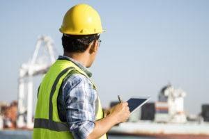 Un ingeniero masculino está inspeccionando el contenedor en el puerto.
