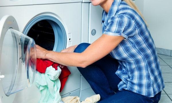 Una mujer está lavando su ropa con la lavadora