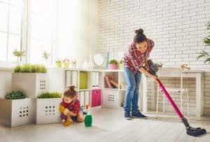 Una mujer joven y una niña están limpiando el polvo y aspirando el suelo