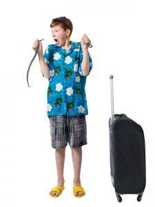 Niño joven en camisa azul y pantalones cortos sostiene una serpiente en sus manos y gritando