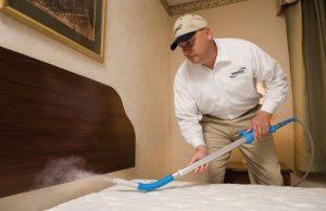El hombre está fumigando pesticida en la cama para matar a los bichos de la cama