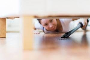 Primer plano de la mujer feliz con el piso de limpieza aspiradora debajo del sofá en casa.