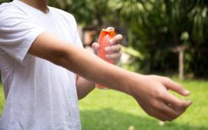 Un hombre está ahorrando repelente de insectos en su brazo