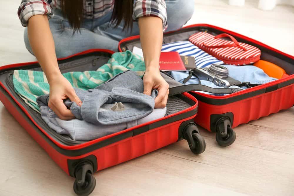 Una mujer está empacando su equipaje