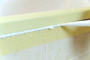 El trabajador coloca sellador de silicona para sellar la unión entre la bañera y la pared.