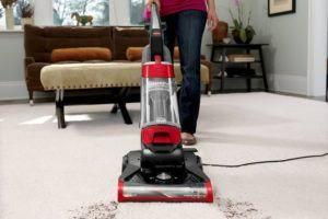 Una mujer está usando aspiradora limpiando el suelo