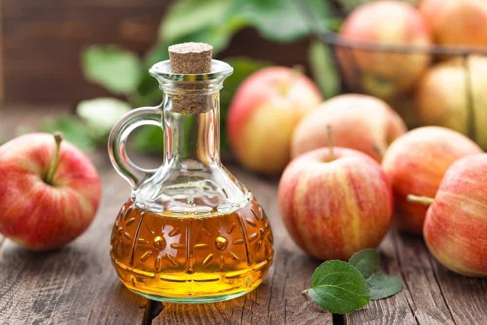 Manzanas y un tazón de manzana Vinagre sobre mesa de madera