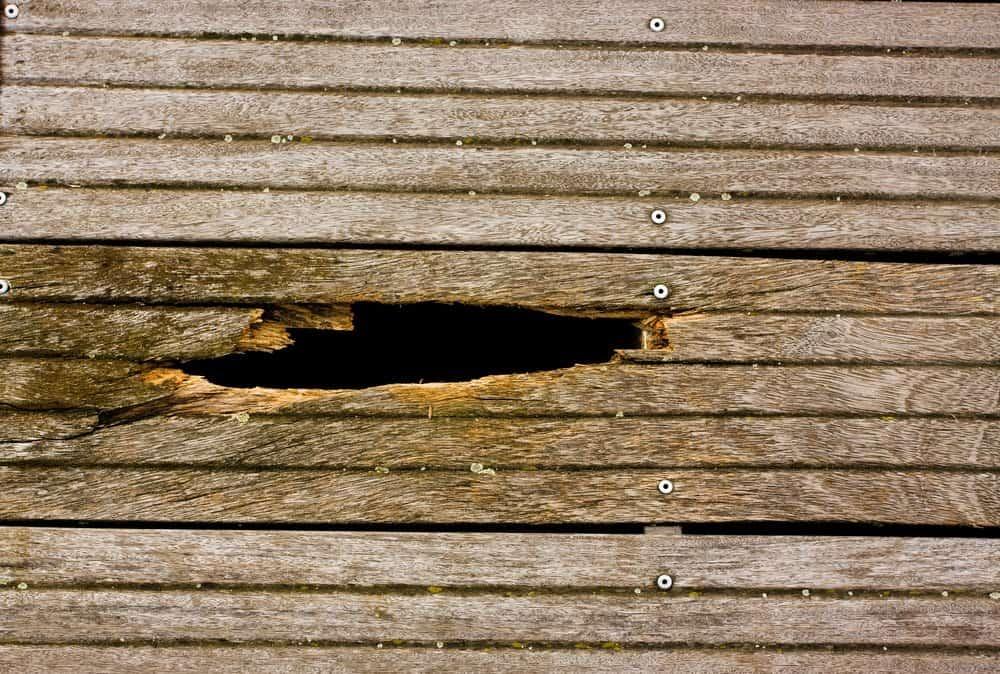 Un gran agujero en la pared de madera