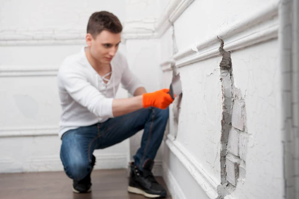 Un hombre apuesto está sellando grietas de la pared