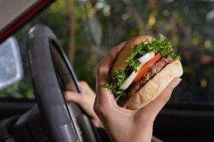 Comer hamburguesa en coche mientras conduce
