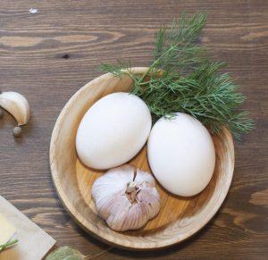 huevos y ajo en el cuenco de madera