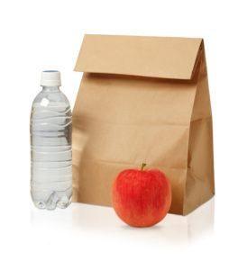 primer plano de la bolsa de almuerzo de papel marrón, manzana roja y botella de agua aislada en blanco.