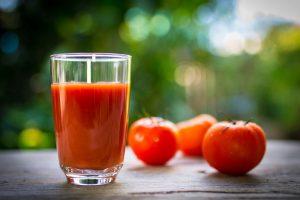 tomates y jugo de tomate en la mesa de madera.