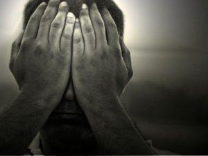 Las manos del hombre cubriendo su afeitado sentimiento deprimido